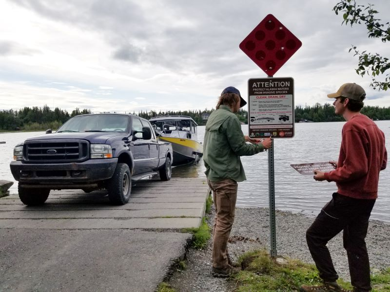 People install invasive species sign at boat launch.